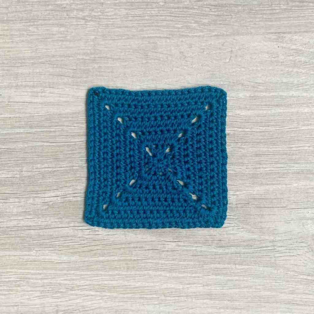 the back or wrong side of a blue solid linked granny square lays on a grey wood effect surface
