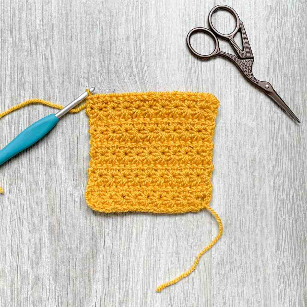 A swatch of yellow crochet star stitch lies on a grey wood effect surface, with a turquoise crochet hook still attached. A pair of scissors sits off to the side