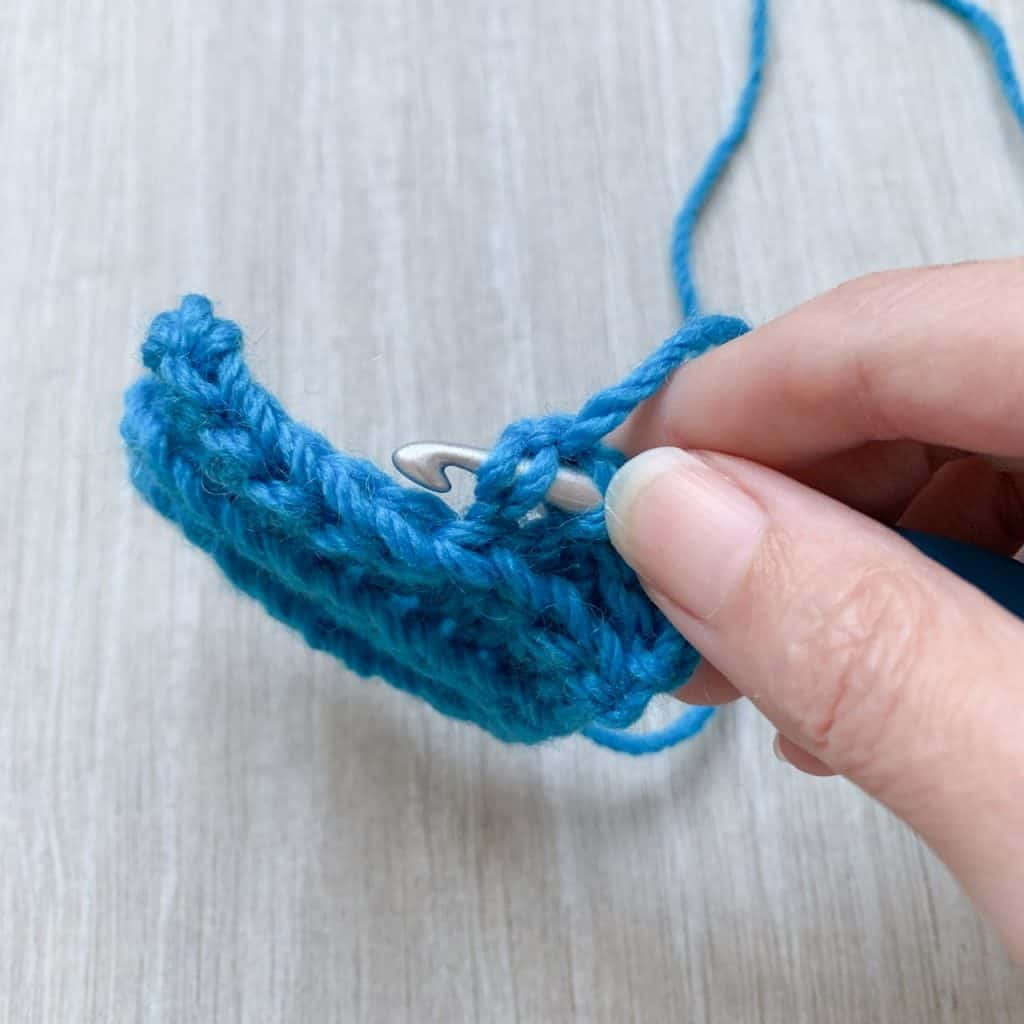 A close up of where to insert the hook into a blue swatch when working a foundation half double crochet stitch