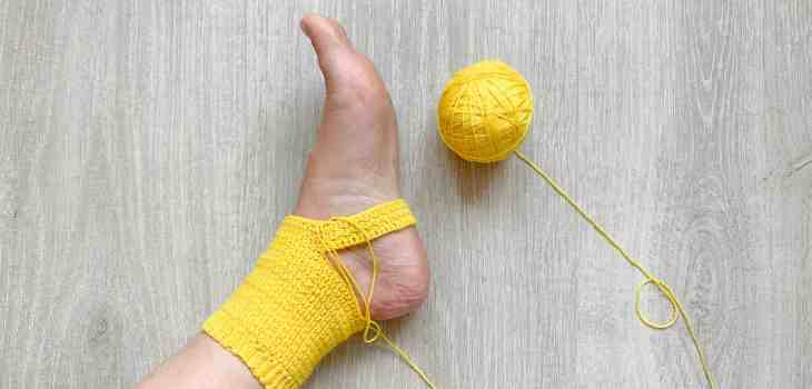 A foot is shown wearing a yellow, half made crochet sock with the ball of yarn still attached