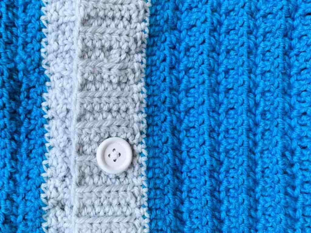 Two vertical pieces of crochet fabric in blue and grey buttoned together with a white wooden button