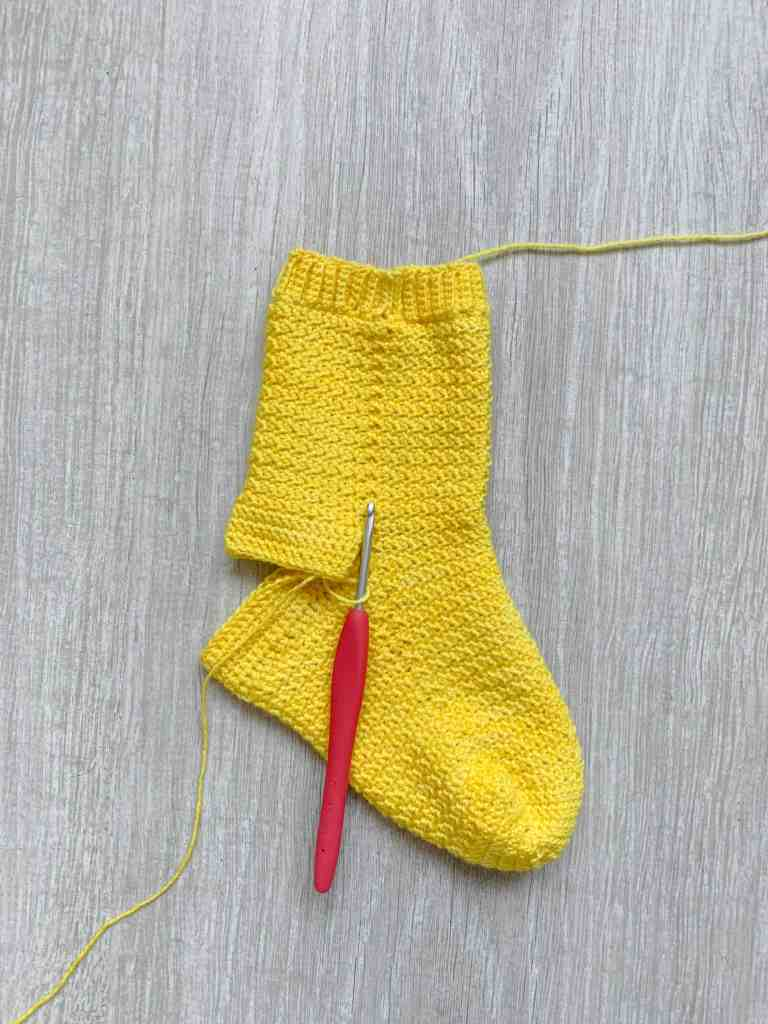 a progress shot of the heel being crocheted into a part made, yellow crochet sock. The red crochet hook is still attached