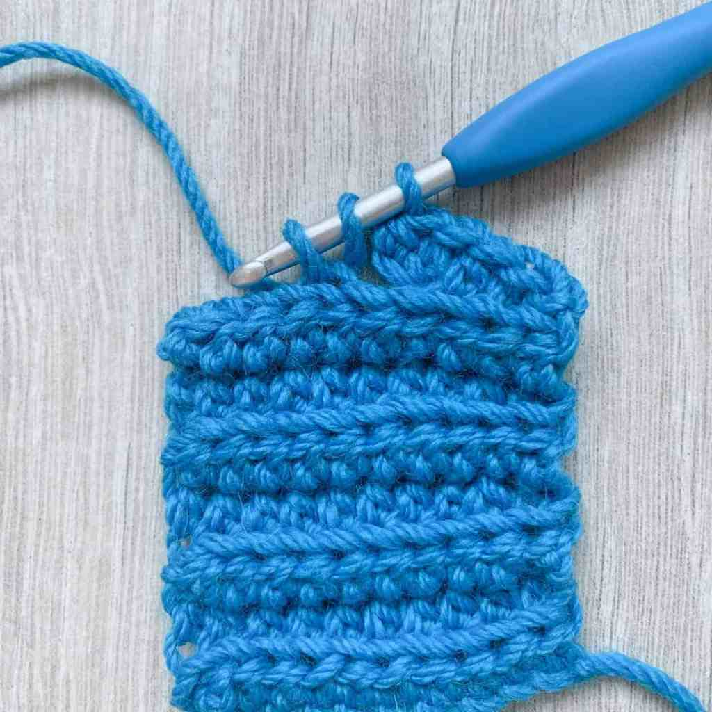 A swatch of blue ribbed crochet showing working in the back loop only to hide the button hole