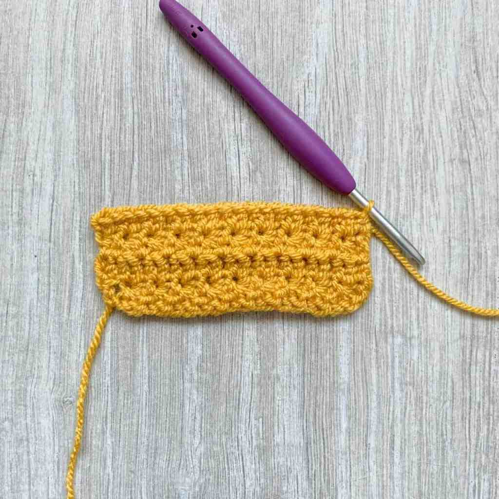 4 rows of a swatch of crochet start stitch worked in yellow yarn with a purple hook lies on a grey surface with the wrong side of the fabric facing. A purple crochet hook is still attached