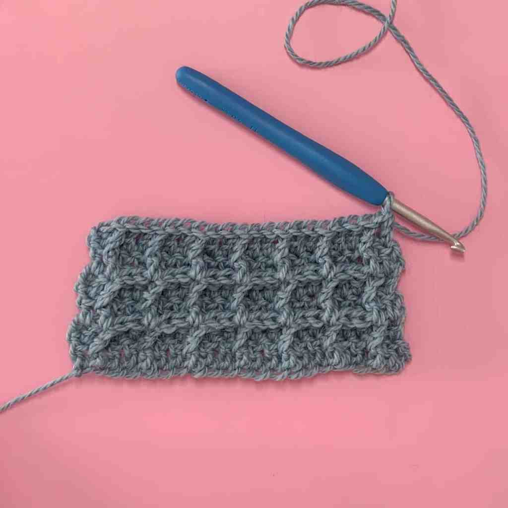 A waffle stitch swatch crocheted in blue yarn and laid on a pink background