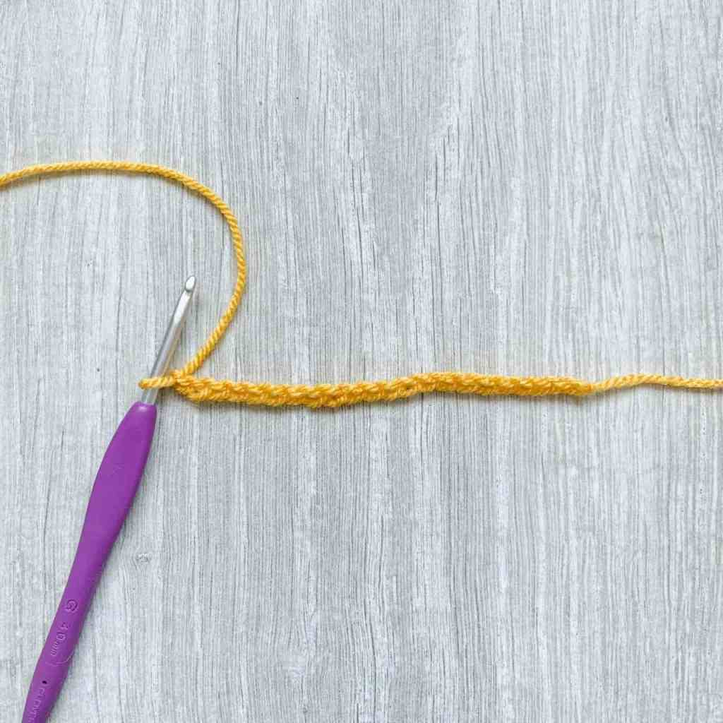 A crochet chain of 22 stitches worked in golden yellow yarn with a purple crochet hook