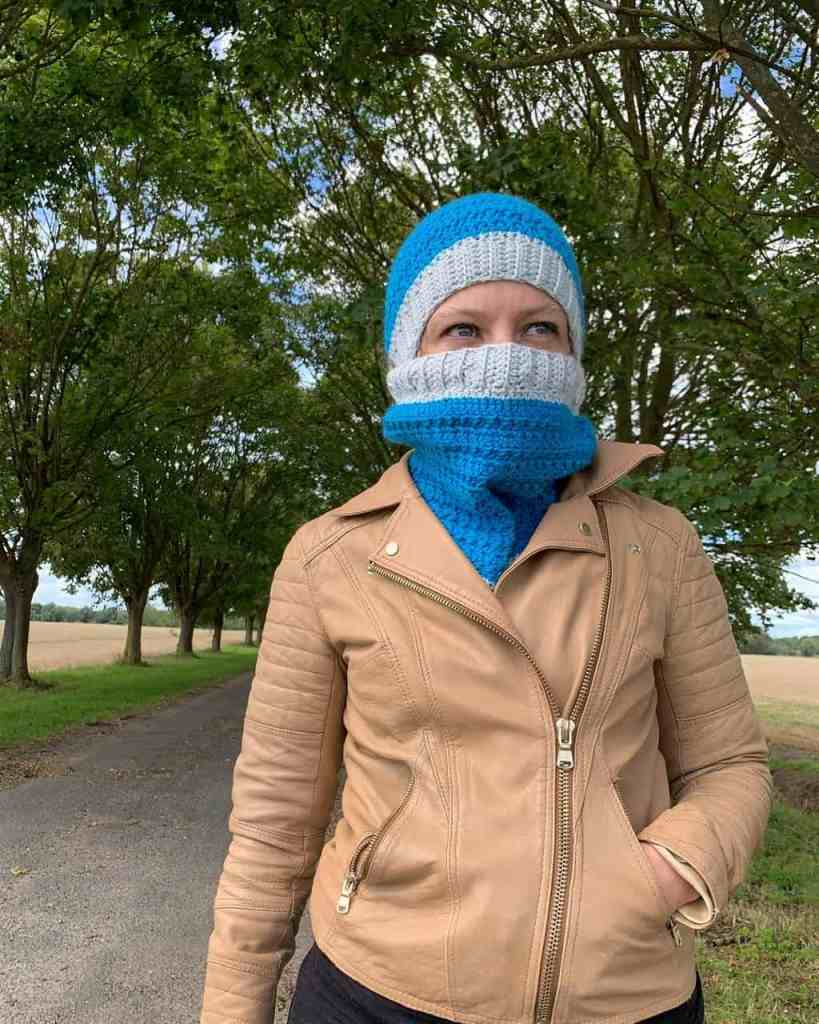 A woman stands in front of an avenue of trees in a turquoise hat and cowl that covers her face. Her hand is in the pocket of a tan leather jacket