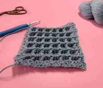 Part way through the second row repeat of crochet waffle stitch being demonstrated with blue yarn. The swatch lies on a pink surface