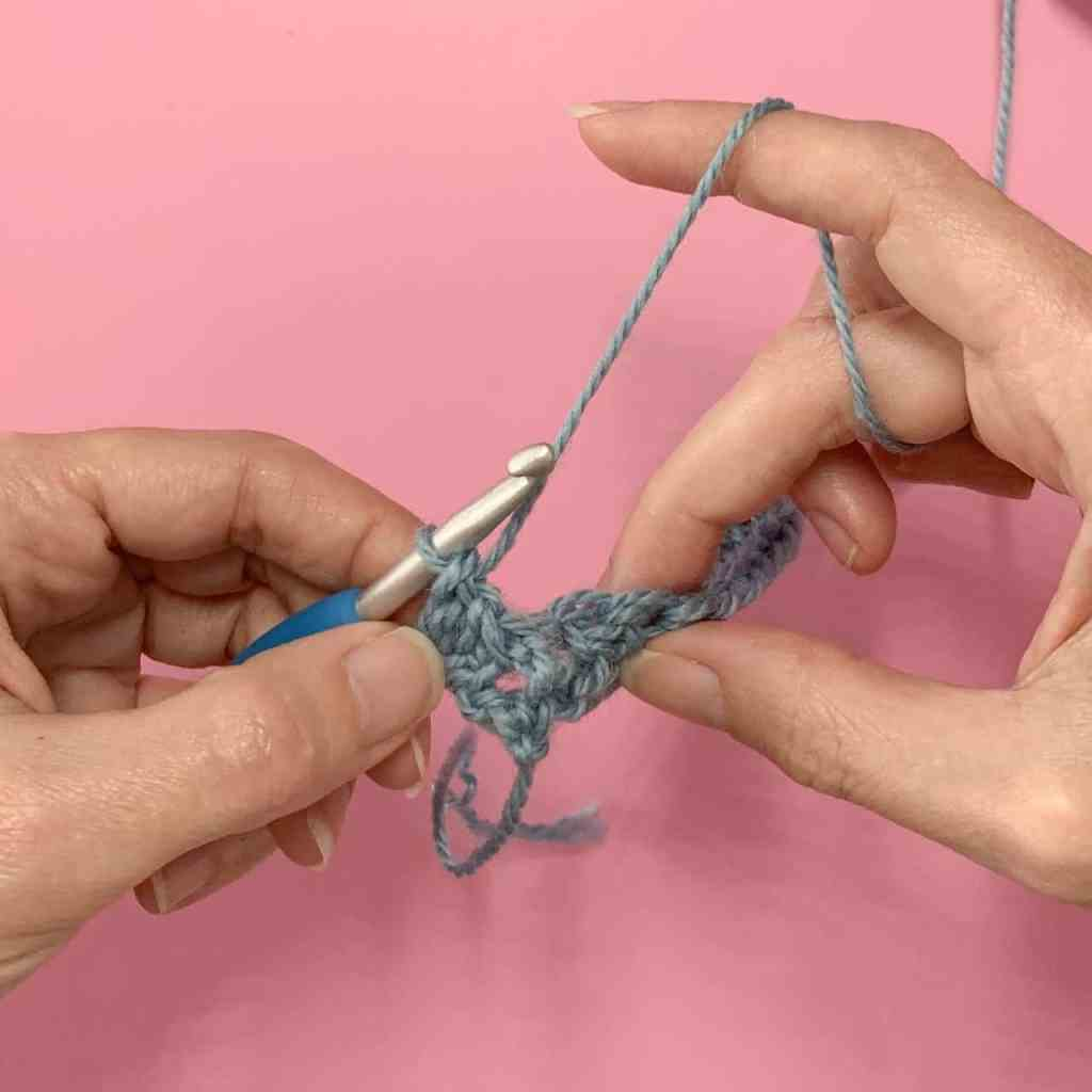 Two hands holding a crochet swatch demonstrate a front post double crochet stitch using blue yarn hovering over a pink background