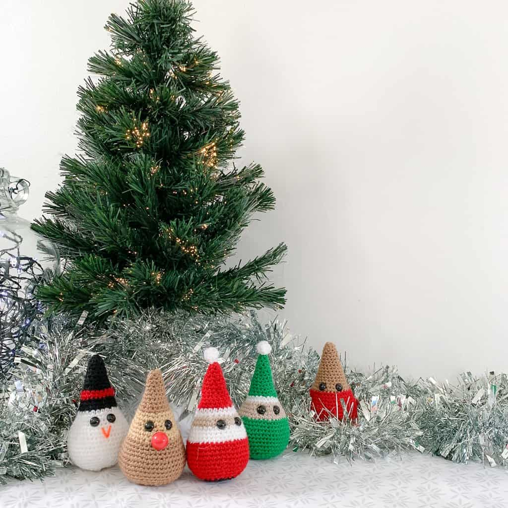 crochet Christmas decorations representing an elf Santa, a snowman, a Reindeer and a robin are gathered round the base of a small Christmas tree with silver tinsel on a white and grey surface
