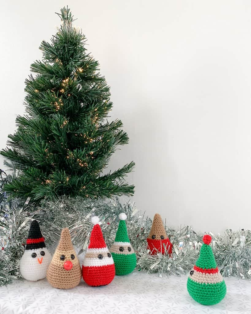 crochet Christmas decorations representing elves Santa, a snowman, a Reindeer and a robin are gathered round the base of a small Christmas tree with silver tinsel on a white and grey surface
