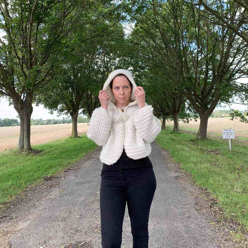 A woman wearing black jeans and a natural wool crochet hooded cape stands in a tree lined avenue with fields to either side. She is holding the sides of the hood either side of her face