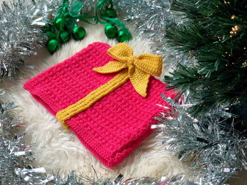 a pink crochet gift shaped christmas hat, with yellow ribbon and bow, lies on a sheepskin rug under a Christmas tree surrounded with green bells and tinsel