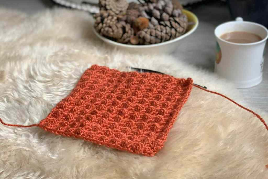 A burnt orange swatch of crochet blanket stitch lies on a sheep skin rug with a bowl or pine cones and a cup of tea blurred in the background. A black crochet hook is just visible attached to the swatch