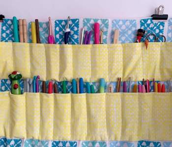 A variety of crochet hooks sit in a colourful hook roll which is hung from a wall using bulldog clips