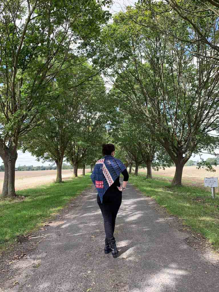 A woman stands in the centre of a tree lined avenue wearing all black with a blue, cream and pink crochet shawl wrapped around her shoulders. She is walking away from the camera