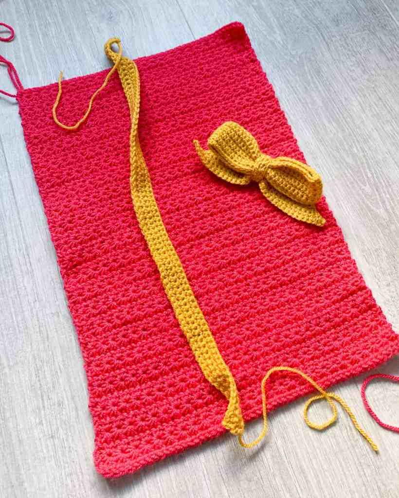 A pinky red rectangle of crochet star stitch fabric lays on a grey wood effect surface with a mustard yellow 'crochet ribbon' and crochet bow on top of it