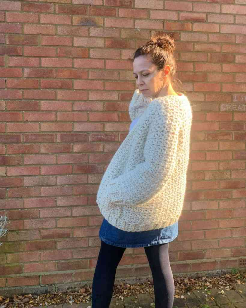 A woman wearing a cream chunky crochet cardigan and a denunciation skirt stands in front of a brick wall, her back is to the camera and she has one hand in her pocket as she starts to turn her head towards the camera
