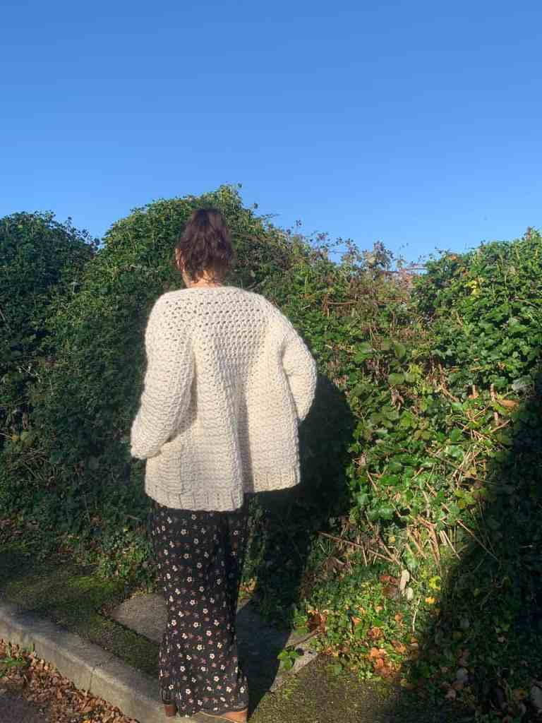 A woman wearing a crochet cardigan and black floral jumpsuit walks, back to the camera, along a curb next to a green hedgerow. The sky is clear blue in the background