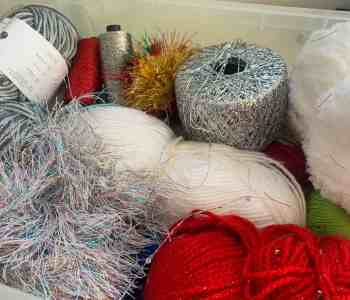 A plastic box full of yarns and threads in silver red, white and sparkly and fluffy textures, all for Christmas crochet