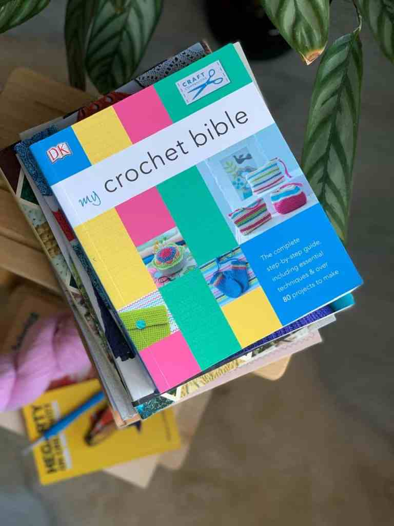 A copy of the 'my crochet bible' book is seen from above on the top of a pile or crochet books stacked on a stool