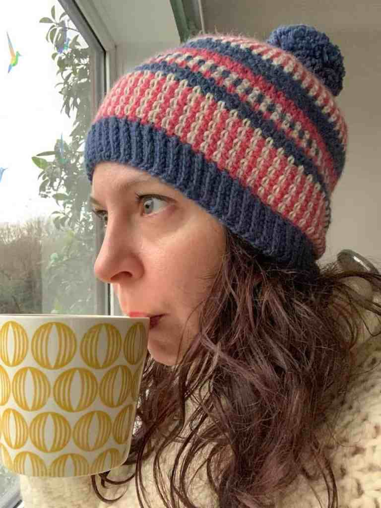 A close up of Dora wearing the scandi stash busting crochet beanie hat whilst drinking tea