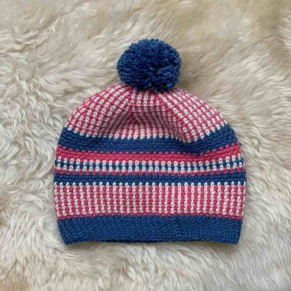 The pink, cream and blue scandi stashbuster crochet beanie hat is seen top down laid flat on a sheepskin rug