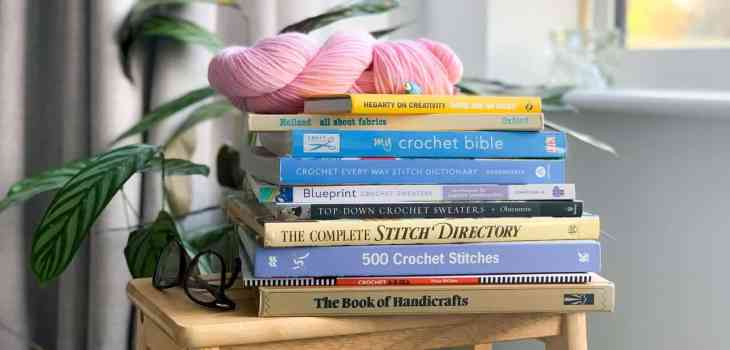 A stack of crochet and stitch directory books sit on top of a wooden stool with a pink hank of yarn and crochet hook on top
