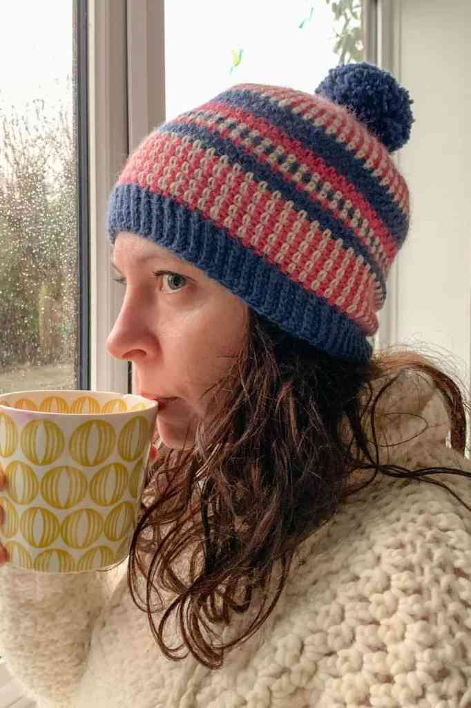 Dora wears the pink blue and cream scandi stashbuster crochet beanie as she sips tea