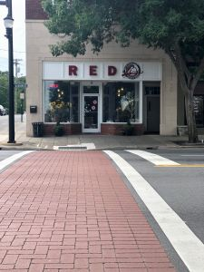 View of a steet crossing. The Redd's Donut store front is across the street with a white sign and red lettering.