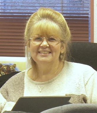 Woman wearing glasses smiling.