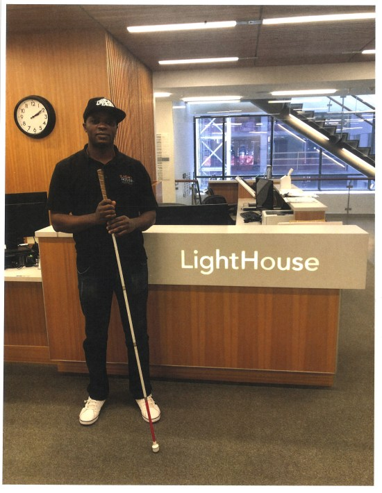 Blind man with cane standing in front of a counter that says LightHouse