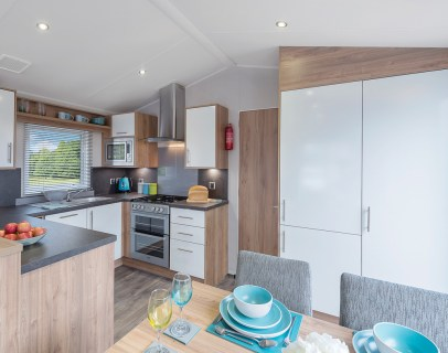 BUILT IN LARGE FRIDGE/FREEZER, DISHWASHER, GAS COOKER, MICROWAVE AND DINING TABLE WITH FOUR CHAIRS
