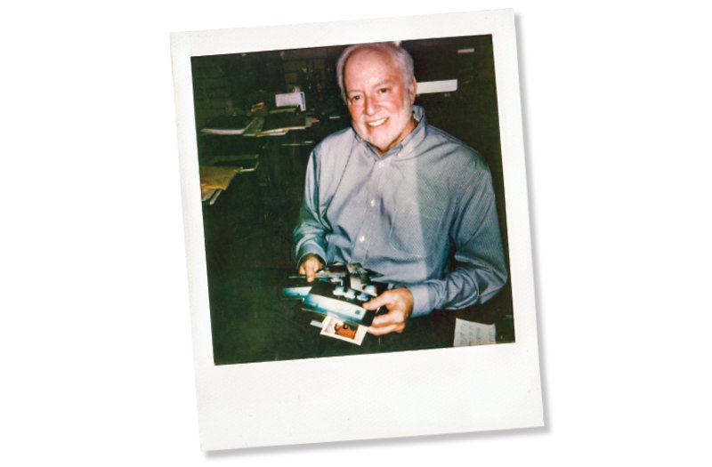 Steven Lamy looks back over Polaroids he took of former students when they first enrolled in his classes — a trick he developed long before student head shots were common practice and one that underpins his legendary ability to remember names and faces. (Photo: Letty Avila.)