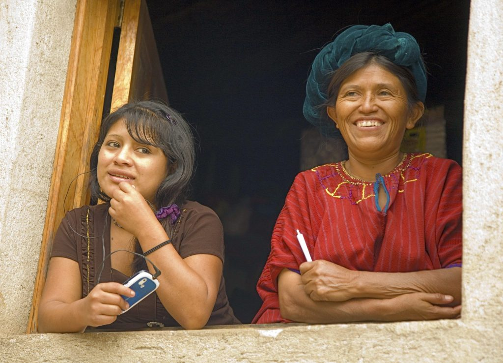 Traditional and Modern woman -ladies - out of their window in Santa Cruz La Laguna