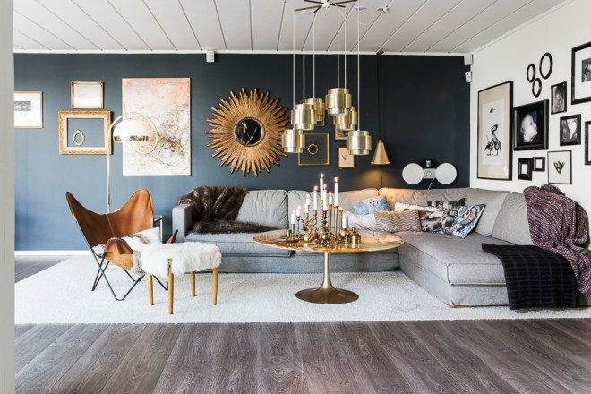 Livingroom with dark blue, a picture wall and lots of brass and also the sun