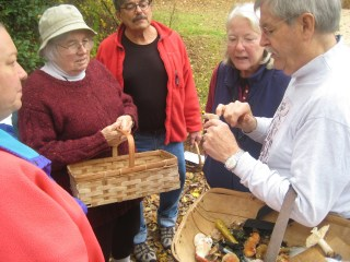 George Davis, right, a local mushroom expert, explains a mushroom to some fellow mushroom hunters.