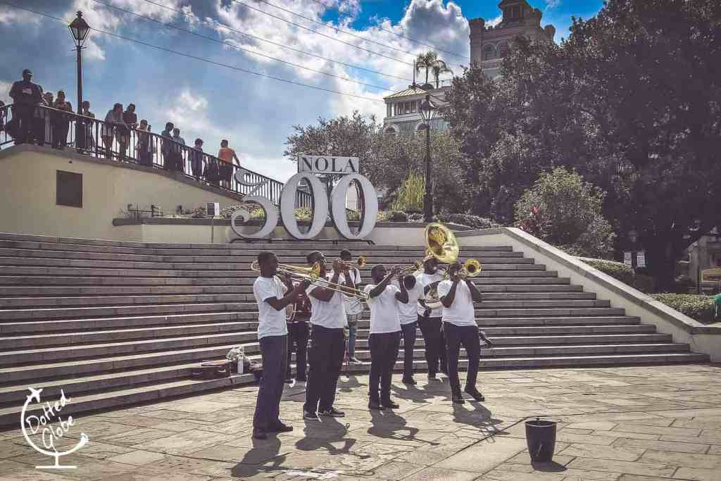 Jazz band playing music in front of sign celebrating New Orleans tricentennial