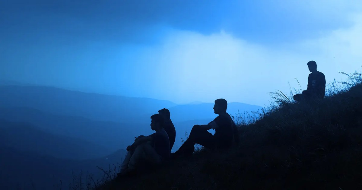 DoubleBlind: Four young adults sitting on a hill on a foggy blue evening.