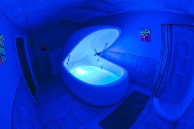 Doubleblind: Photo of a sensory deprivation tank with blue neon light. In this article, Doubleblind looks at 5 ways to trip without psychedelics.
