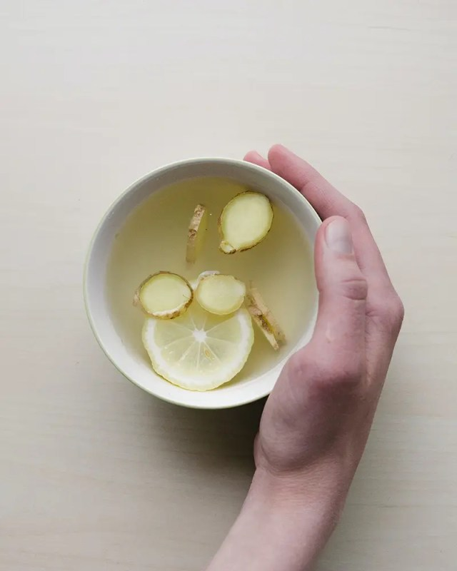 DoubleBlind: Image of hand holding cup of lemon and ginger tea. In this article, DoubleBlind explore lemon tekking, a way of consuming shrooms.