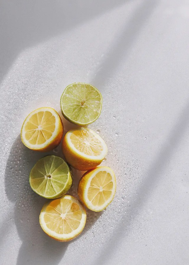 DoubleBlind: Image of halved lemons and limes laying on white table. In this article, DoubleBlind explore lemon tekking, a way of consuming shrooms.