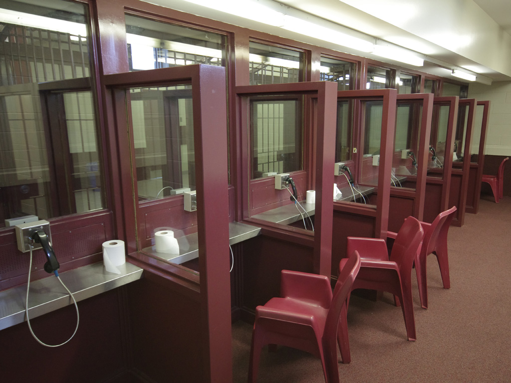 Stock photo of a prison waiting room with three empty red chairs and rolls of toilet paper at each booth.