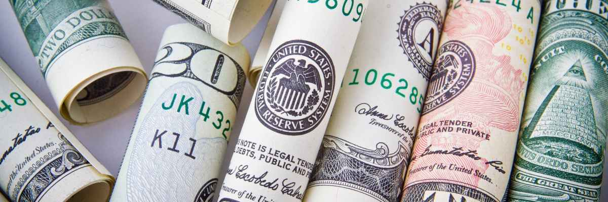 A series of rolled up twenty dollar bills arranged as if they were about to be used as a straw with which to snort drugs