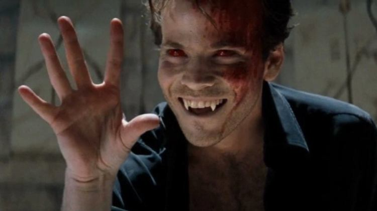 Still from the 1998 film Blade. Pictured is the character Deacon Frost, played by Stephen Dorff, with bloodshot red eyes and bruises on his face, holding his hand out in front of him with his palm outstretched