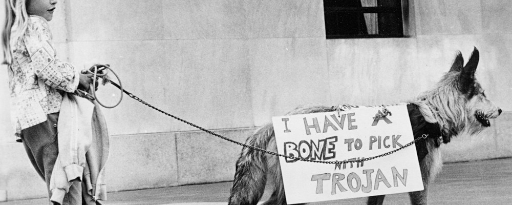 """A young girl holds the leash of a dog wearing a sign that reads """"I have a bone to pick with trojan"""" at an anti-nuclear protests at the oregon capitol in Salem"""