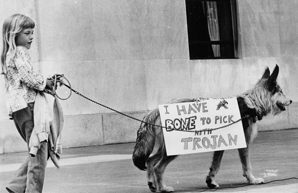 """Black and grey photo of a young girl holding a sweater in one hand. In the other, she's holding a very cute dog on a leash, which is wearing a sign that reads """"I Have a Bone to Pick with Trojan"""""""