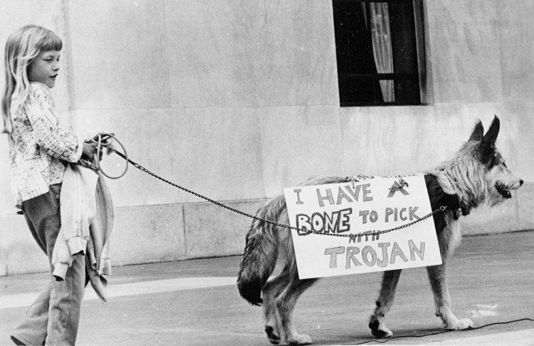 "Black and grey photo of a young girl holding a sweater in one hand. In the other, she's holding a very cute dog on a leash, which is wearing a sign that reads ""I Have a Bone to Pick with Trojan"""