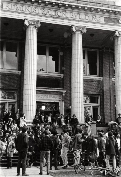 Black and grey photograph depicting maybe 50 to 60 university students gathered on the steps of Johnson Hall on campus. It's hard to make out the faces, but one can tell that there's a band set up on the steps and lots of bicycles in the foreground.