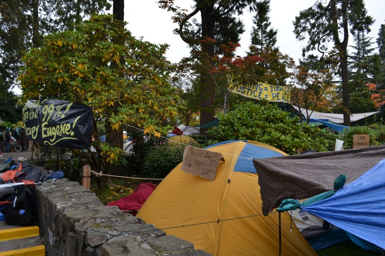 "Color photograph of a yellow and blue tent with a cardboard sign that reads ""free haircuts"" with an arrow pointing to the tent. The tent is set among the trees around the park blocks, which have signs that read ""caring equals justice, justice equals peace"" and ""we are the 99 percent, occupy eugene!"""
